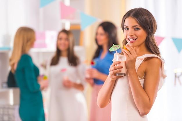 少女はカクテルを飲んで、正面に笑みを浮かべて立っています。 Premium写真