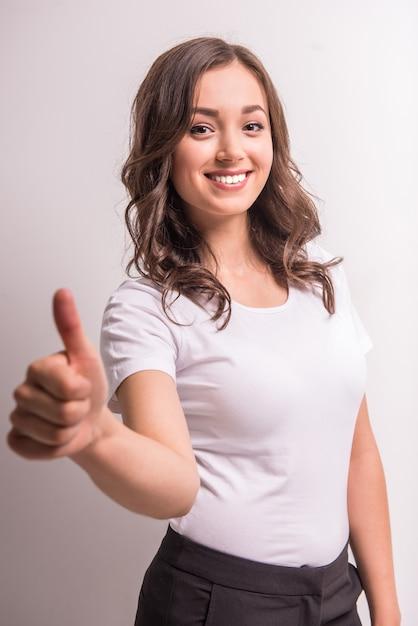 女性は親指を現して、正面を見ています。 Premium写真