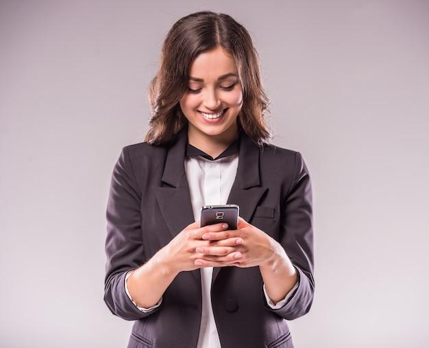 若い女性は、スマートフォンでメッセージを書いています。 Premium写真
