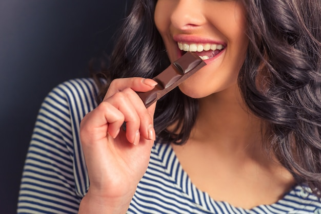 チョコレートを食べて、笑顔の魅力的な女の子。 Premium写真