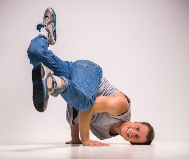 巧みなブレイクダンサーがスタジオで彼の手でポーズします。 Premium写真