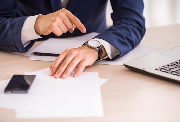 Руки молодого бизнесмена указывает на часы. Premium Фотографии
