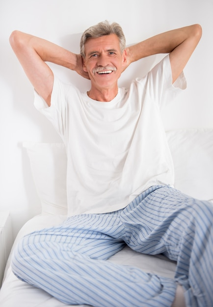 Жизнерадостный старший человек сидит в кровати и смотрит камеру. Premium Фотографии