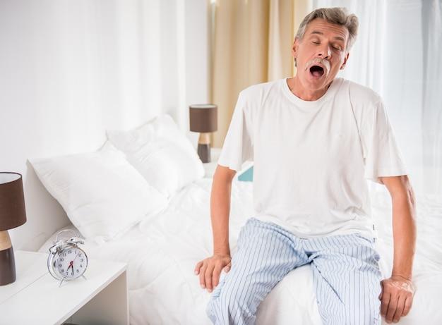 年配の男性はベッドに座っているとあくびです。 Premium写真