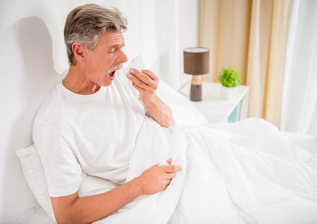 年配の男性が鼻をかむ、彼は風邪をひいています。 Premium写真