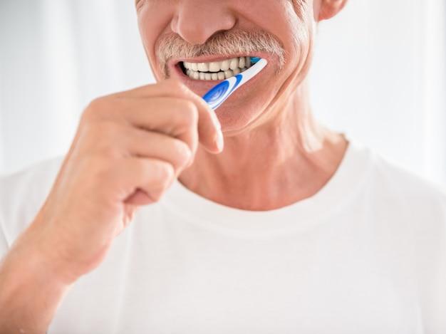 年配の男性は彼の歯を掃除し、笑っています。 Premium写真