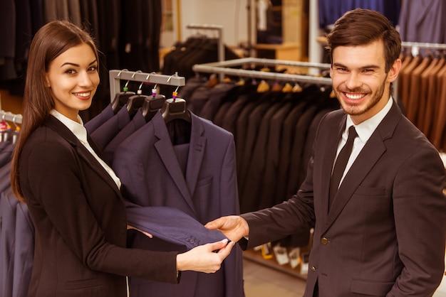 若い美しい女性店員コンサルティング男。 Premium写真