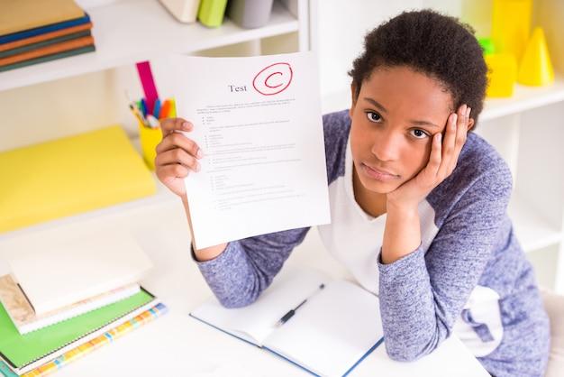 Несчастная школьница мулата сидит за столом. Premium Фотографии
