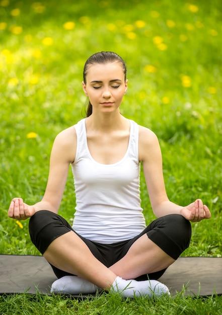 夏の公園のマットの上に座って、ヨガをやっているスポーティな女の子 Premium写真