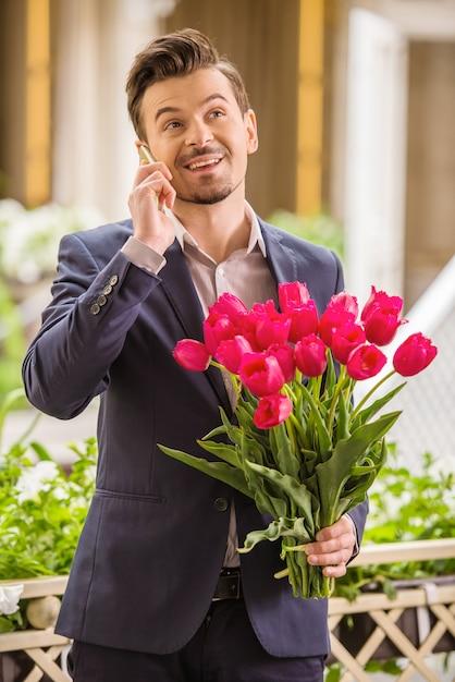 Мужчина держит букет из тюльпанов и разговаривает по телефону. Premium Фотографии