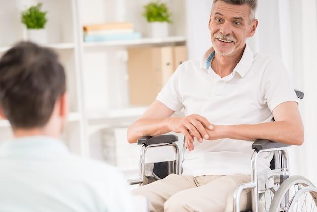 自宅で座っていると、高齢の父親と話している成人男性。 Premium写真