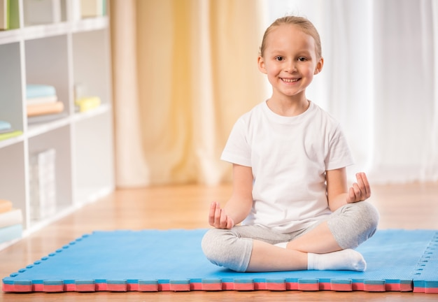 運動マットの上に座っている少女。 Premium写真