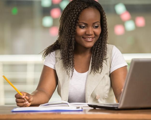 Привлекательная африканская женщина, сидя за столом. Premium Фотографии