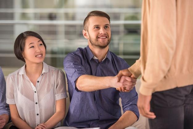 オフィスでの会議中に握手する同僚。 Premium写真