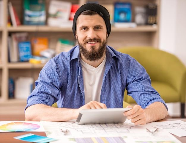 Человек одет случайные сидя за столом и с помощью цифрового планшета Premium Фотографии