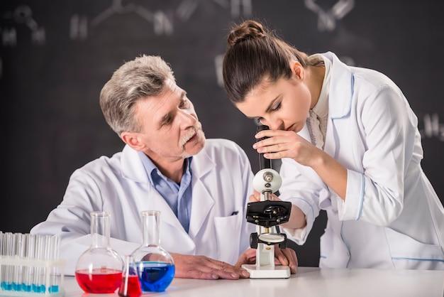 教授はアマランスの顕微鏡を見てくれます。 Premium写真