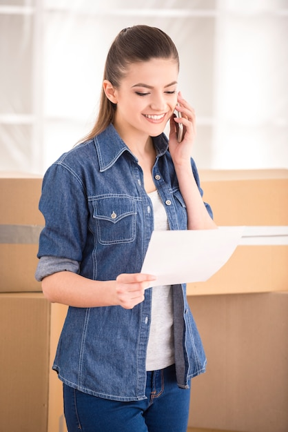 新しい家に移動する運送会社を呼び出す幸せな女。 Premium写真