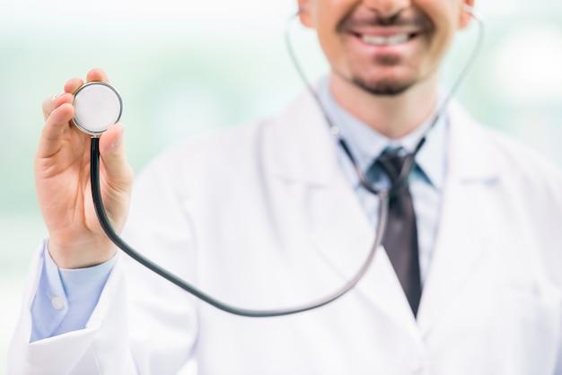 聴診器を押しながら笑みを浮かべて男性医師のクローズアップ。 Premium写真