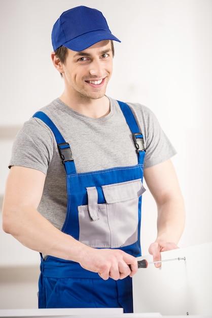 家の内部で修復ツールを使用して修理の笑みを浮かべてください。 Premium写真