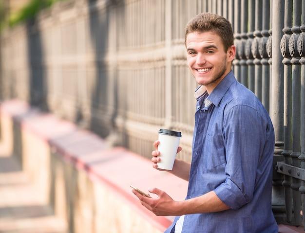 Молодой красивый мужчина держит его телефон и чашка кофе. Premium Фотографии