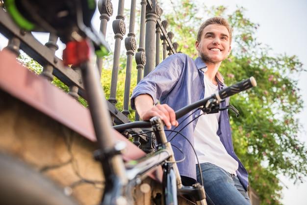 街で自転車で立っている若い男。 Premium写真