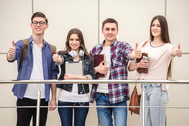 親指を現して幸せな若い学生のグループ。 Premium写真