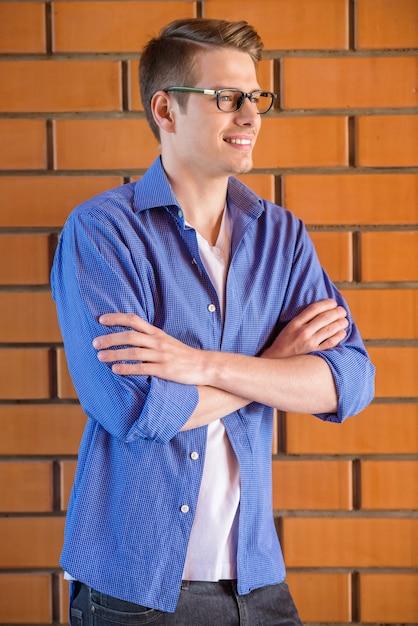 スマートカジュアルな服装でハンサムな若い男の側面図です。 Premium写真