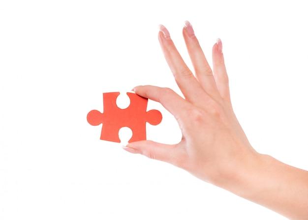 パズルを持っている女性の手のクローズアップ。 Premium写真