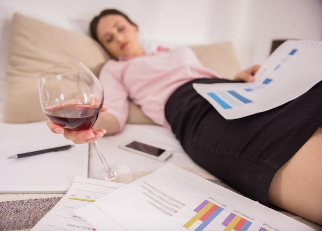 Утомленная молодая женщина спать на кровати с бокалом вина. Premium Фотографии