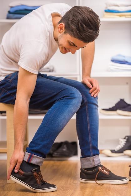 Красивый мужчина надевает обувь, сидя на стуле. Premium Фотографии