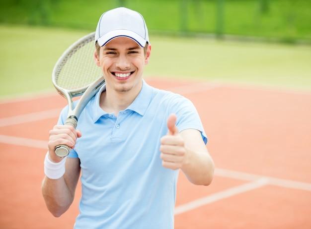 男は親指を表示し、テニスラケットを保持しています。 Premium写真