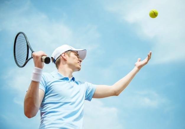 Красивый теннисист на жесткий корт, обслуживающих мяч. Premium Фотографии