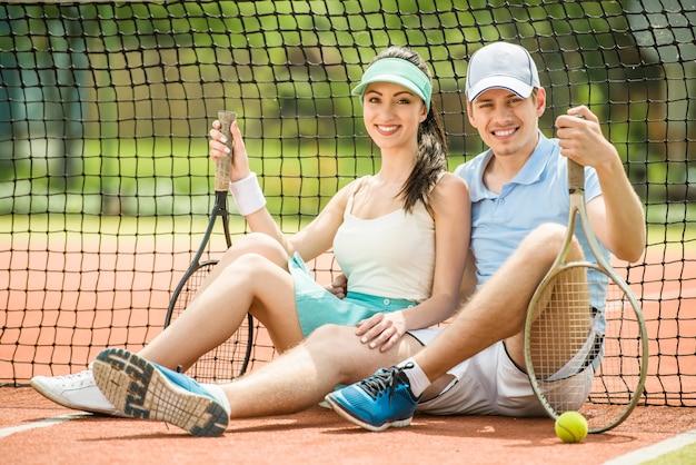 テニスラケットを保持しているテニスコートに座っている若いカップル。 Premium写真