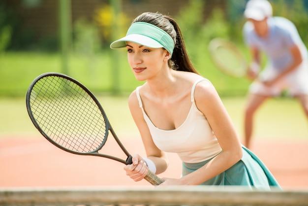 テニスコートでカップルがダブルスをプレーします。 Premium写真