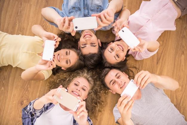 Друзья с смартфонов, лежа на полу в кругу. Premium Фотографии
