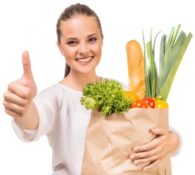 親指を現して、買い物袋を保持している女性。 Premium写真