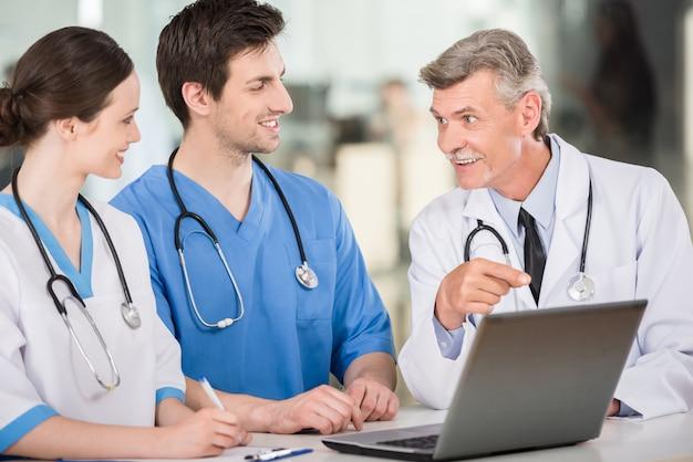 Врачи работают вместе на ноутбуке в кабинете врача. Premium Фотографии