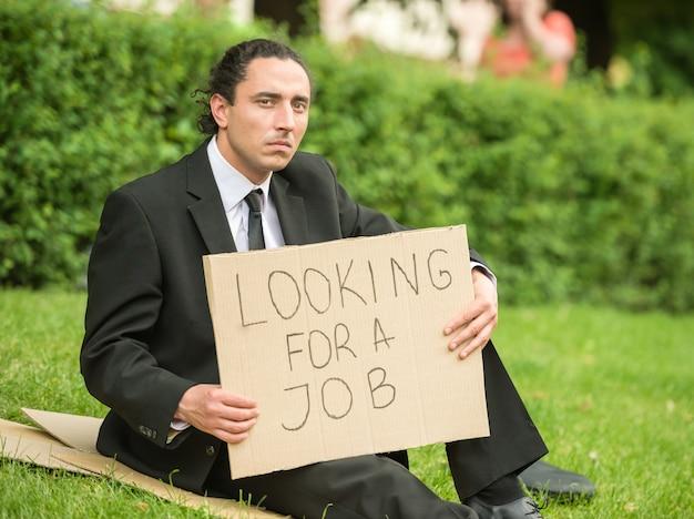 芝生に座ってサインと欲求不満の失業者。 Premium写真