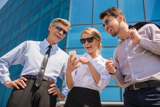 Три успешных деловых людей в костюмах, глядя на телефон. Premium Фотографии