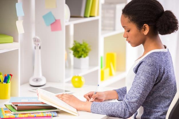 若い可愛いムラート女子高生はテーブルに座っています。 Premium写真