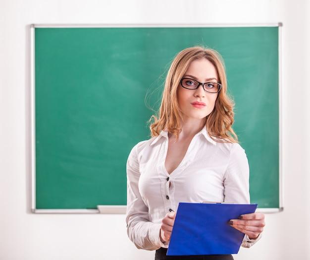 教室でメモを保持している先生。 Premium写真