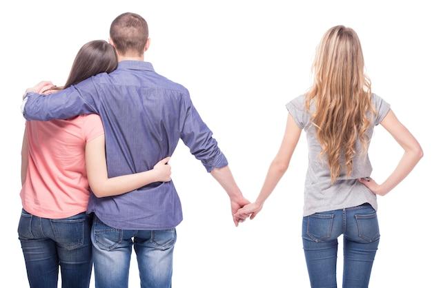 男は別の女の子に手をつないで彼のガールフレンドを抱きしめます。 Premium写真