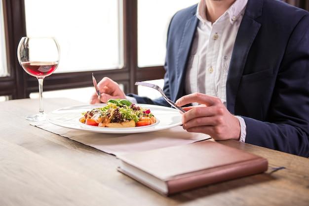 レストランでのビジネスランチ中に食べるビジネスマン。 Premium写真