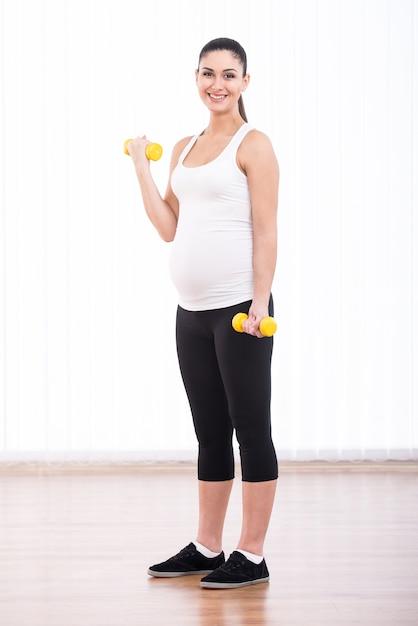 妊娠中の女性は、ダンベルでスポーツをしています。 Premium写真