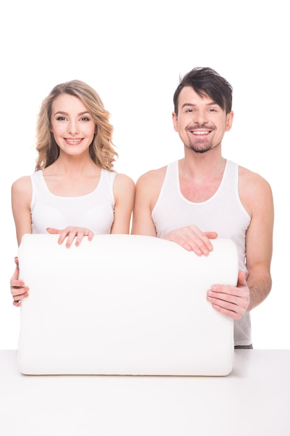 Красивая молодая пара с качественной мягкой подушкой. Premium Фотографии