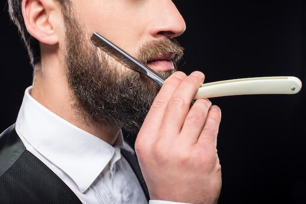ストレートかみそりで若い残忍なひげを生やした男の側面図。 Premium写真