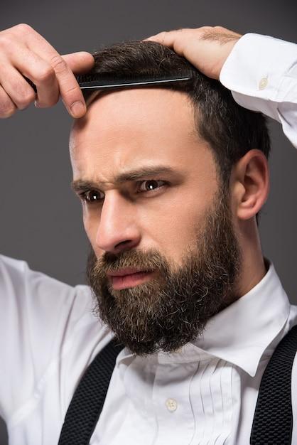 Портрет молодой жестокой бородатый человек с бритвой. Premium Фотографии