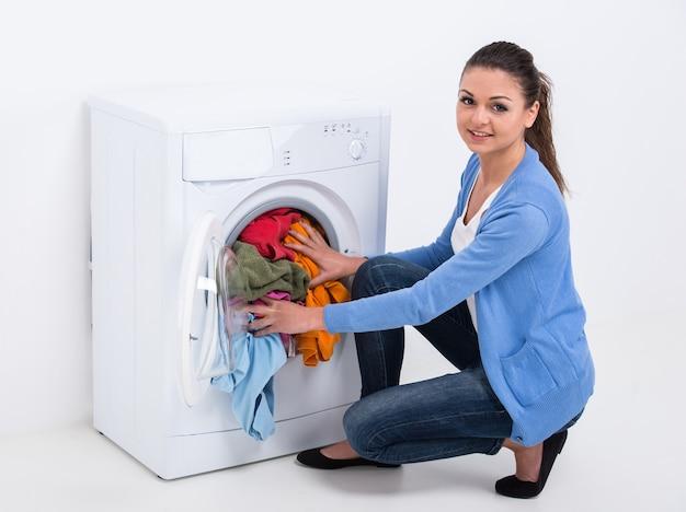 若い主婦は洗濯機で洗濯をしています。 Premium写真
