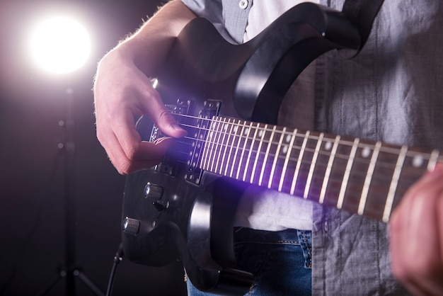 Макро руки молодого человека играет на гитаре. Premium Фотографии