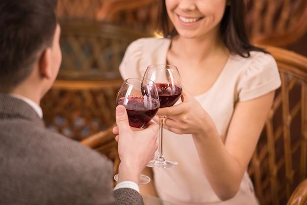 若い幸せなカップルのロマンチックなデートは、赤ワインのグラスを飲みます。 Premium写真